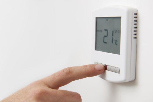 Chauffagiste Aubervilliers - Un homme règle la température de son thermostat