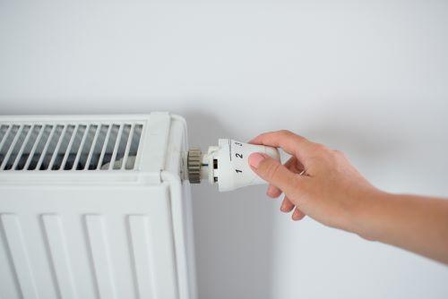 Chauffagiste Besançon - Une femme règle un radiateur.