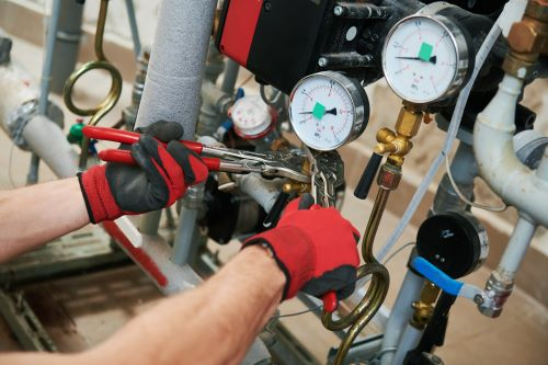 Chauffagiste Dijon - Un chauffagiste répare la tuyauterie