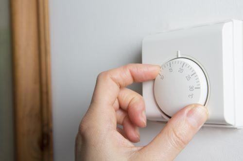 Chauffagiste Dunkerque - Un homme règle la température de son thermostat