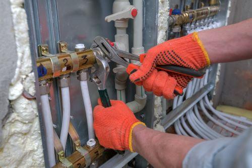 Chauffagiste Grenoble - Un artisan répare un système de chauffage.