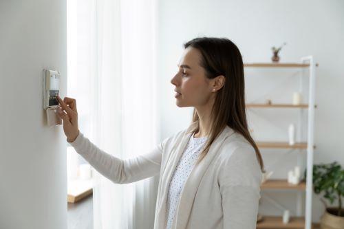 Chauffagiste Mulhouse - Une femme règle le chauffage de sa maison.