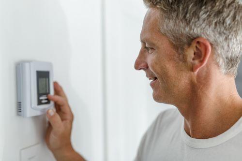 Chauffagiste Nice - Un homme règle la température de son thermostat