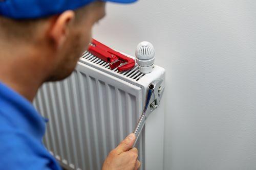 Chauffagiste Nîmes - Un chauffagiste répare un radiateur
