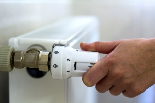 Chauffagiste Perpignan - Un artisan règle un radiateur.