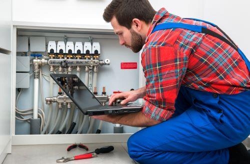 Chauffagiste Rennes - Un chauffagiste fait des vérifications sur un système de chauffage.