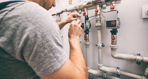 Chauffagiste Roubaix - Un homme installe un système de chauffage dans une maison.