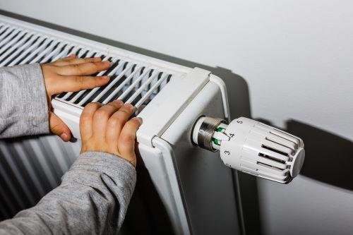 Chauffagiste Rouen - Une personne se réchauffe auprès d'un radiateur.