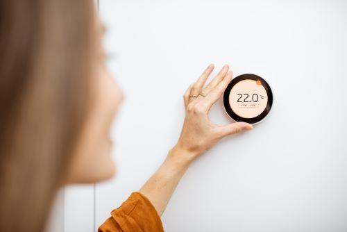 Chauffagiste Rouen - Une femme règle la température de sa maison.