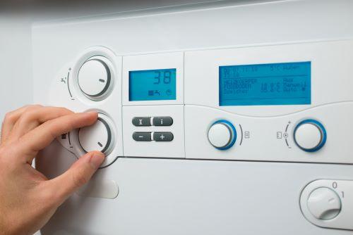 Chauffagiste Tourcoing - Un homme règle la température de son thermostat