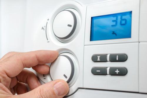 Chauffagiste Tous - Un homme règle la température de son thermostat
