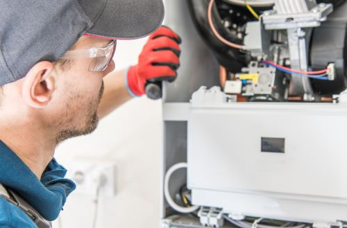 Chauffagiste Le Havre - Un chauffagiste inspecte un chauffe-eau