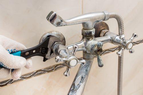 Plombier Artigues-près-Bordeaux - Un plombier répare un robinet de douche.
