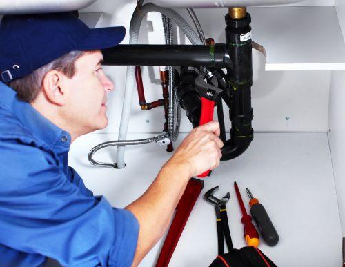 Plombier Bouliac - Un plombier répare la tuyauterie d'un lavabo