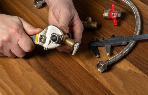 Plombier Carbon-Blanc - Un plombier installe un tuyau flexible en acier inoxydable.