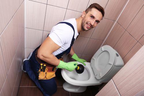 Plombier Fargues-Saint-Hilaire - Un plombier procède au débouchage d'un WC