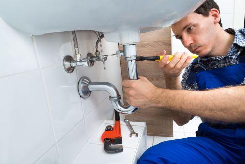 Plombier Gignac-la-Nerthe - Un artisan répare le siphon d'un robinet.
