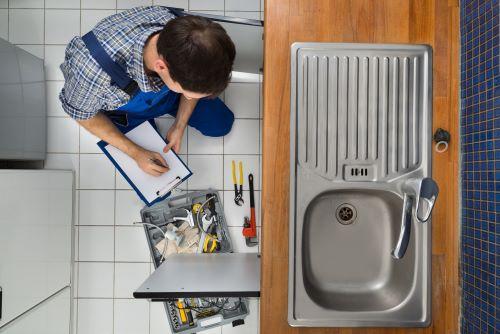 Plombier Gignac-la-Nerthe - Un plombier fait des installations dans une cuisine.