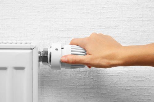 Plombier Le Haillan - Une femme règle la température de son chauffage