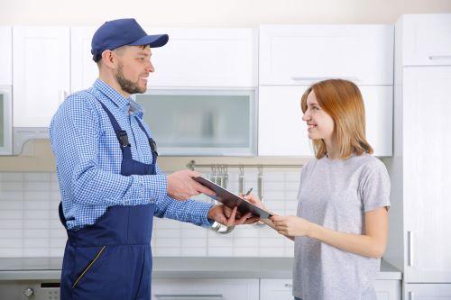Plombier Pompignac - Un plombier fait signer des documents à une cliente