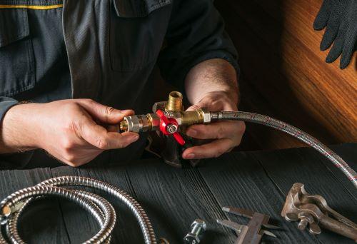 Plombier Quint-Fonsegrives - Un plombier installe un tuyau flexible.