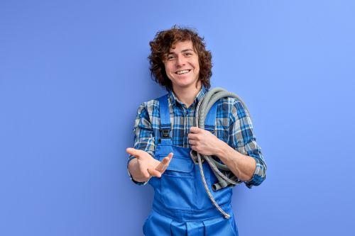 plombier Bègles - un plombier tient des flexibles dans sa main en souriant