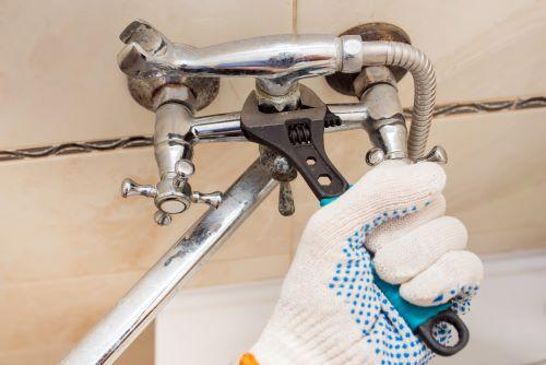 plombier Camblanes-et-Meynac - un artisan installe le robinet d'une baignoire