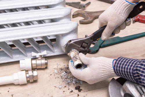 plombier Carignan-de-Bordeaux - un artisan installe un radiateur