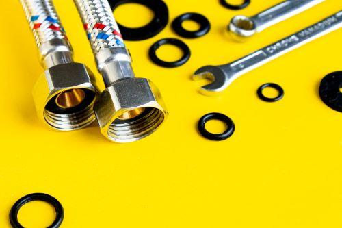 plombier Cénac - des éléments de plomberie sur un fond jaune