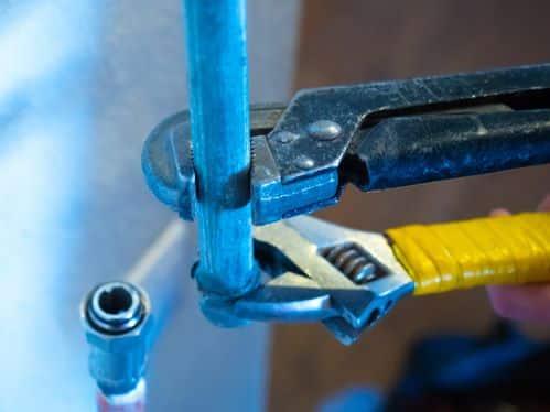 plombier Cormeilles-en-Parisis - un homme installe un tuyau de plomberie