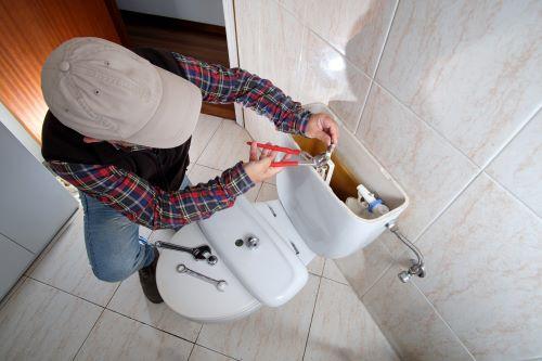 plombier Eaubonne - un homme répare une chasse d'eau