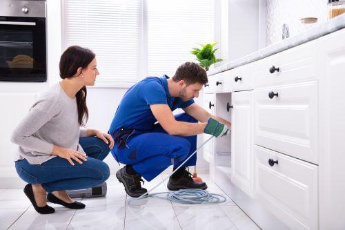 plombier Élancourt - un plombier débouche l'évier d'une cuisine