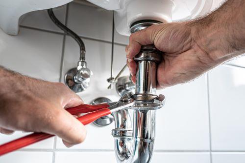 plombier Étampes - un artisan desserre le siphon d'un lavabo