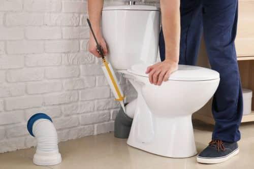 plombier Limeil-Brévannes - un artisan applique du mastic sur une canalisation de WC
