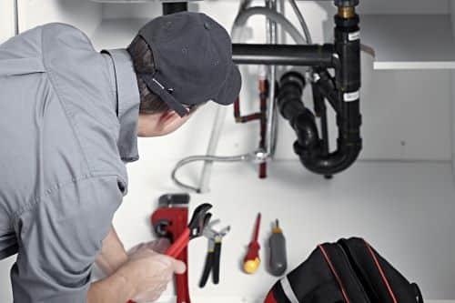 plombier Rambouillet - un artisan installe un appareil sanitaire