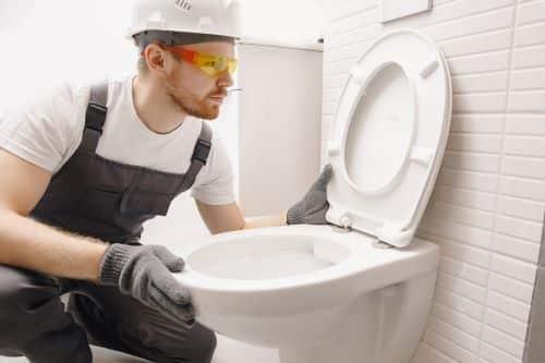 plombier Sèvres - un artisan inspecte des WC suspendus
