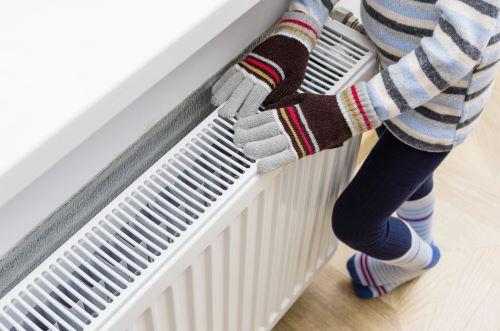 Chauffagiste Antony - Une personne se réchauffe les mains sur un radiateur.