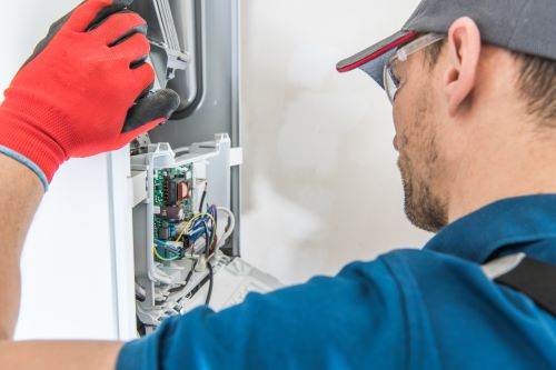 Chauffagiste Arles - Un chauffagiste inspectant un thermostat deffectueux.