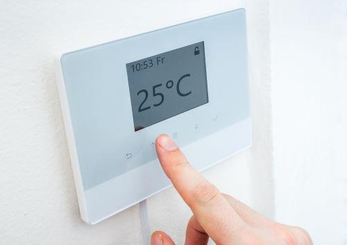 Chauffagiste Aulnay-sous-Bois - Un homme règle la température de son thermostat