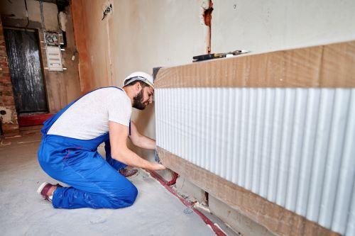 Chauffagiste Béziers - Un artisan installe un radiateur.