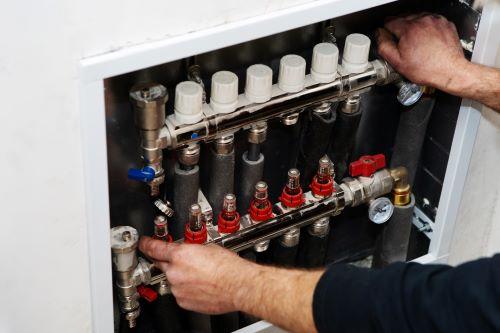 Chauffagiste Calais - Un chauffagiste répare un système de chauffage.