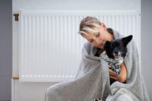 Chauffagiste Cannes - Une femme se réchauffe avec son chien devant un chauffage