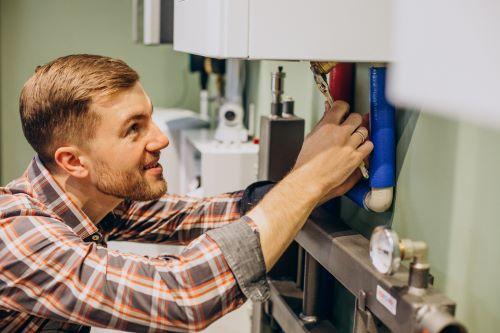 Chauffagiste Chambéry - Un chauffagiste répare un chauffe eau