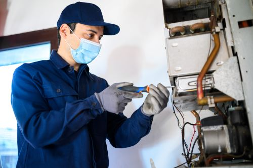 Chauffagiste La Rochelle - Un chauffagiste répare un système de chauffage.