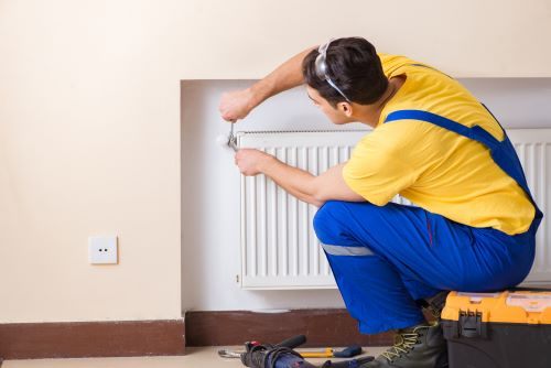 Chauffagiste Levallois-Perret - Un chauffagiste installe un radiateur.