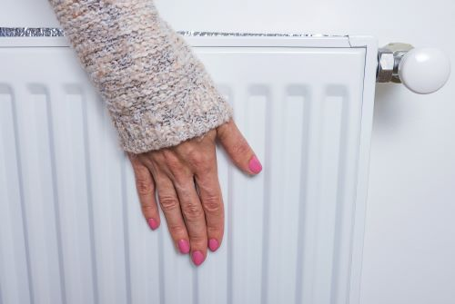 Chauffagiste Mérignac - Un femme a la main posé sur un chauffage