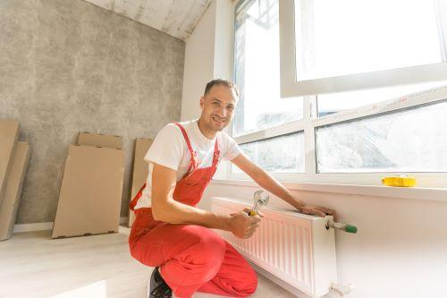 Chauffagiste Montauban - Un chauffagiste installe un radiateur au mur