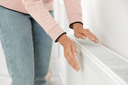 Chauffagiste Neuilly-sur-Seine - Une femme se réchauffe les mains sur un radiateur