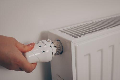Chauffagiste Niort - Une femme règle la température de son chauffage