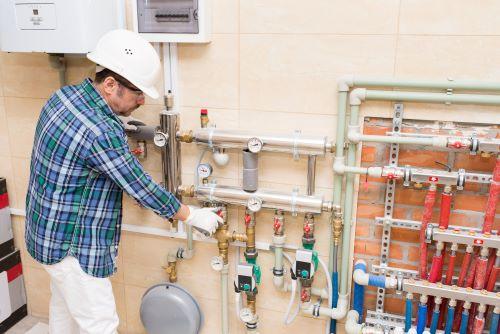 Plombier Attiches - Un plombier règle la tuyauterie